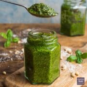 Homemade basil pesto in an open jar with a teaspoon of pesto held above the jar.