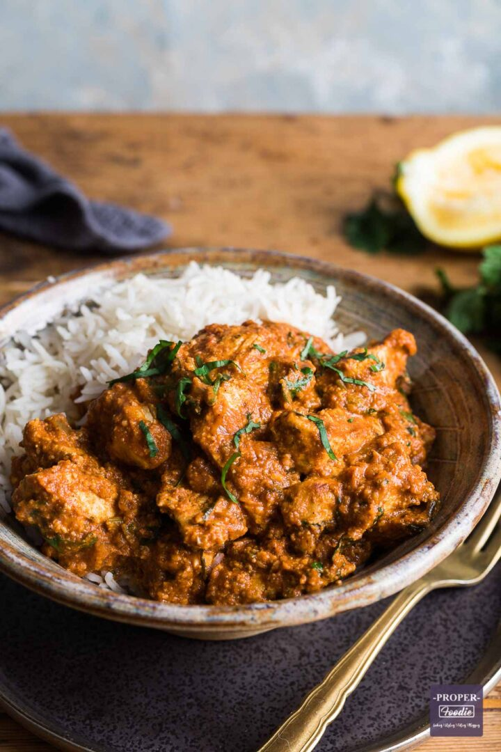Chicken tikka masala curry and rice in a bowl sat on a plate with a gold fork at the side and half a squeezed lemon in the background.