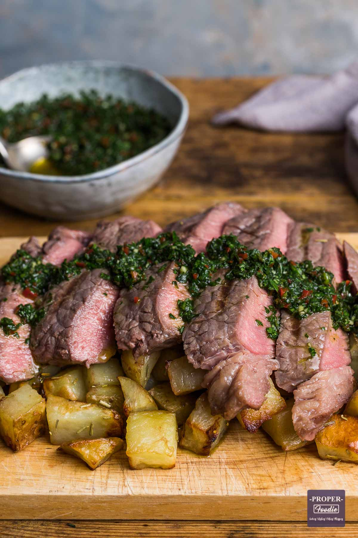 Slices of rump steak cooked medium rare and served over cubed potatoes with a chimichurri dressing drizzled over the top.