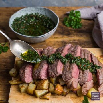 Slices of medium-rare steak positioned over a pile of cubed rosemary potatoes with a herb and chilli dressing being spooned over the top.