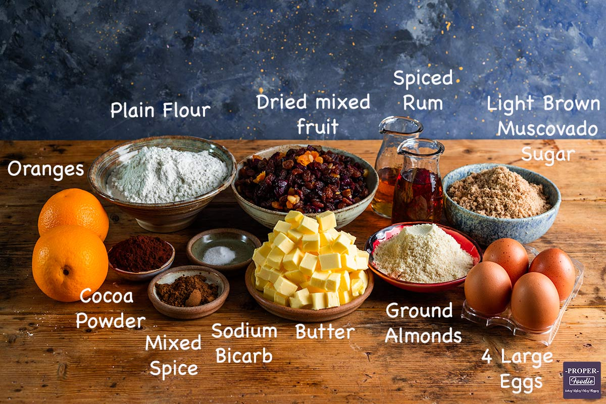 A display of all the ingredients needed to make a Christmas cake with text overlay labelling each ingredient.