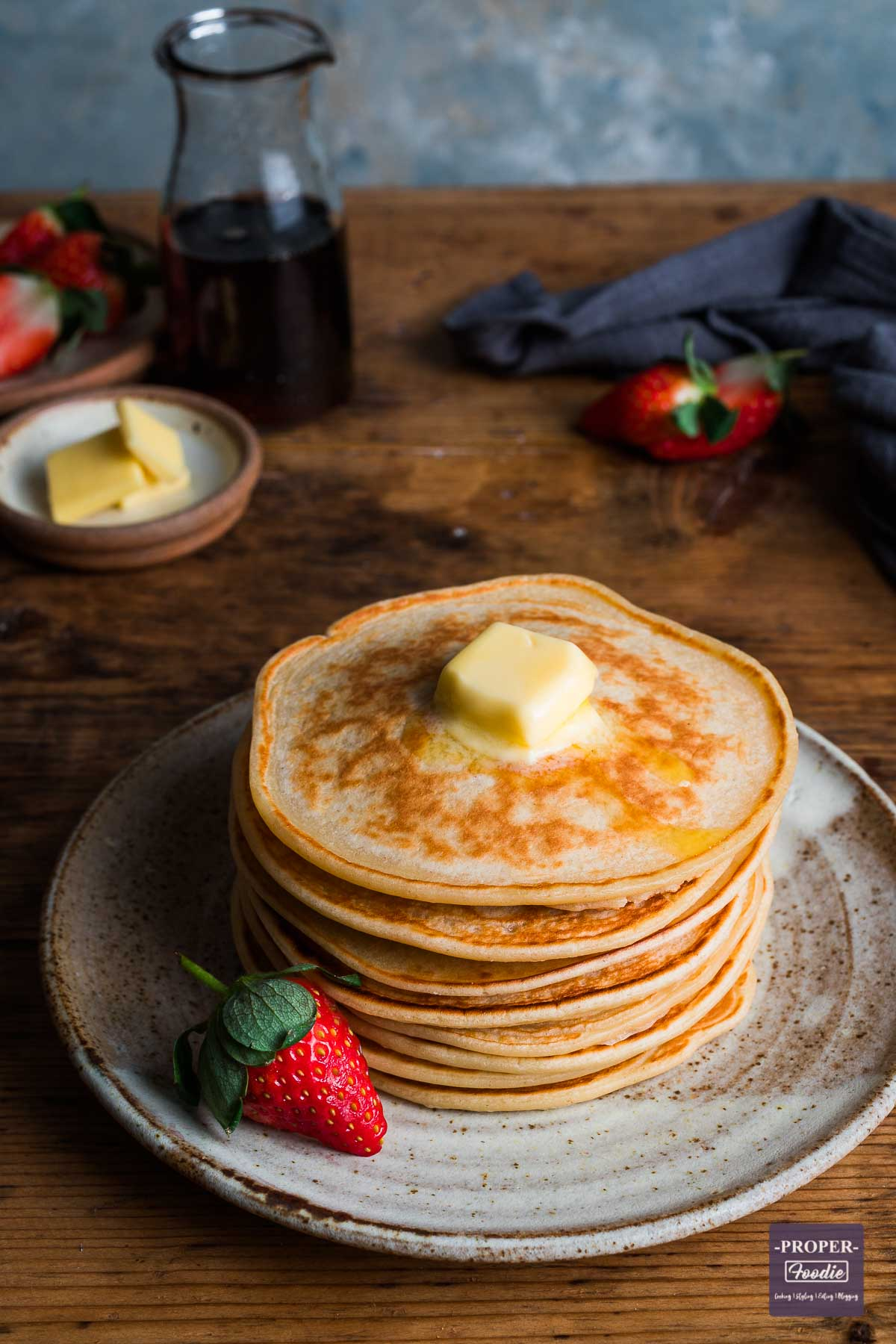 A stack of pancakes on a small plate with butter melting on the top and a small glass jug of syrup in the background.