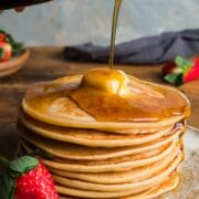 A stack of American pancakes with a piece of butter melting on the top and syrup poured over and drizzling down one side.