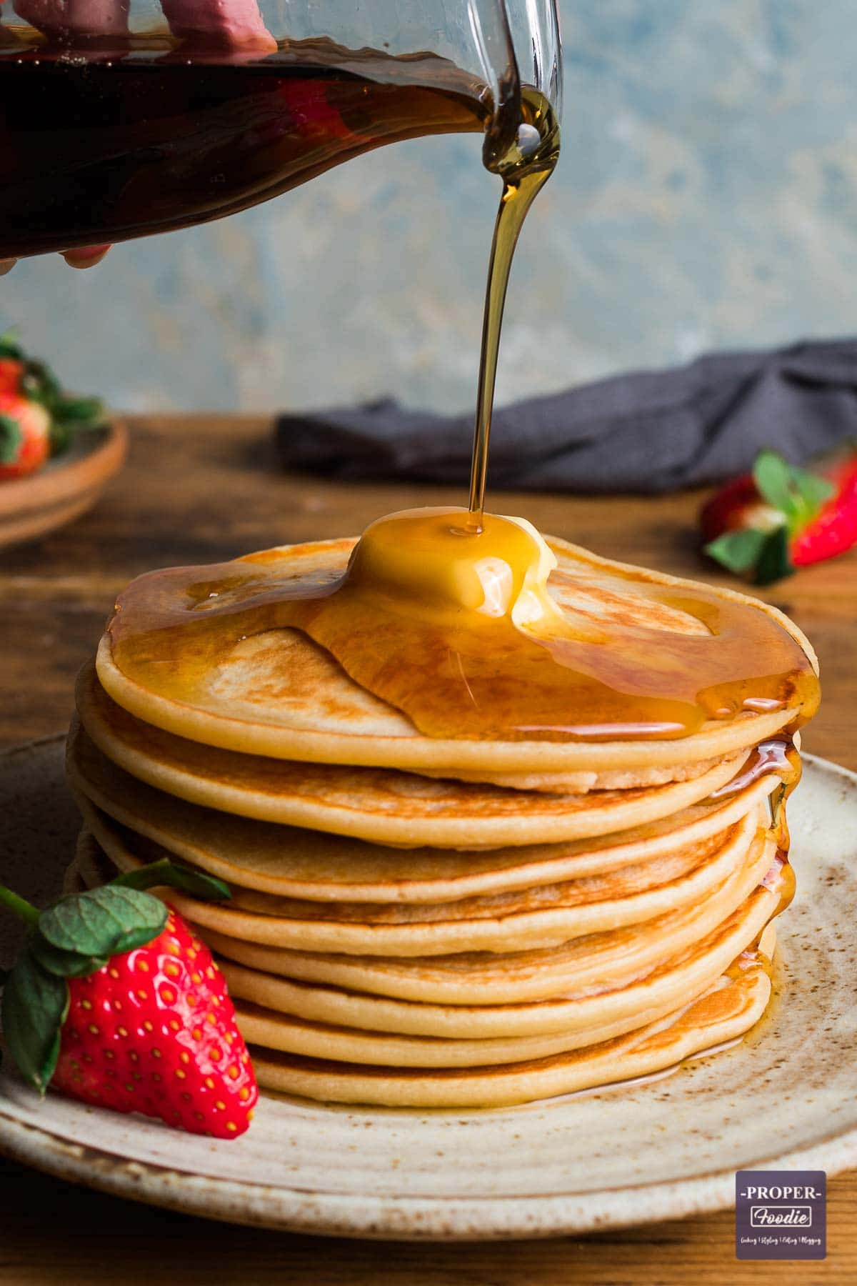 A stack of pancakes with a piece of butter melting on the top and syrup poured over and drizzling down one side.