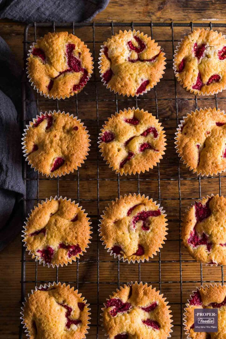 Raspberry and lemon muffins on a wire rack viewed from above with bits of raspberry visible on the top of each muffin.