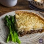 A slice of lamb and mint pie with a pastry base and mash potato topping, served on a plate with tender stem broccoli.