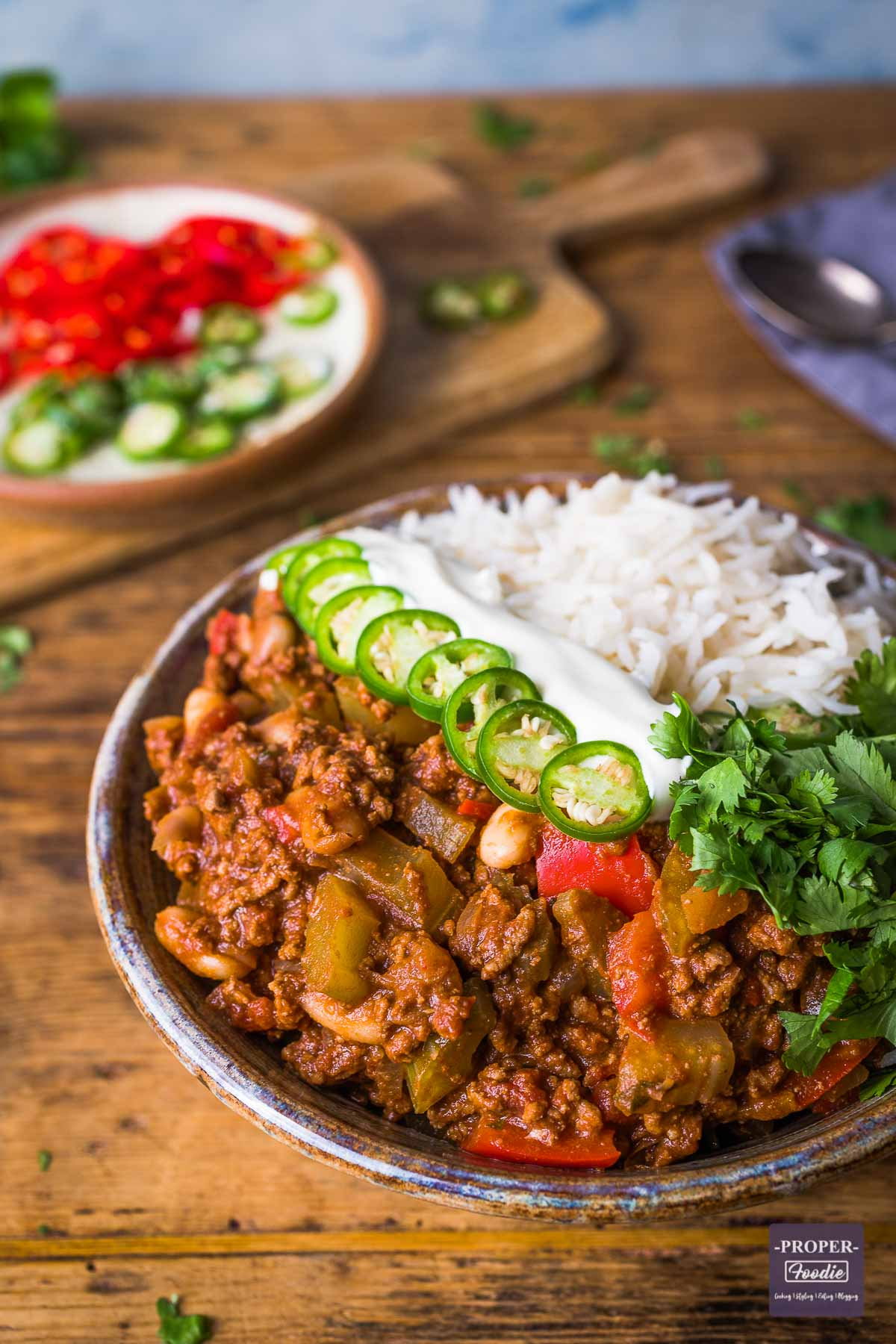 chilli con carne in a bowl with rice, green chillies, soured cream and fresh coriander