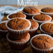 Half of a round cooling rack visible, with pumpkin muffins resting on top in their liners with text overlay: Spiced Pumpkin Muffins.