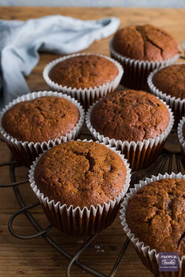 Half of a round cooling rack visible, with pumpkin muffins resting on top in their liners