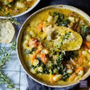 A Tuscan vegetable and bean soup served up in two bowls and topped with crusty bread, grated parmesan and fresh sprigs of thyme.