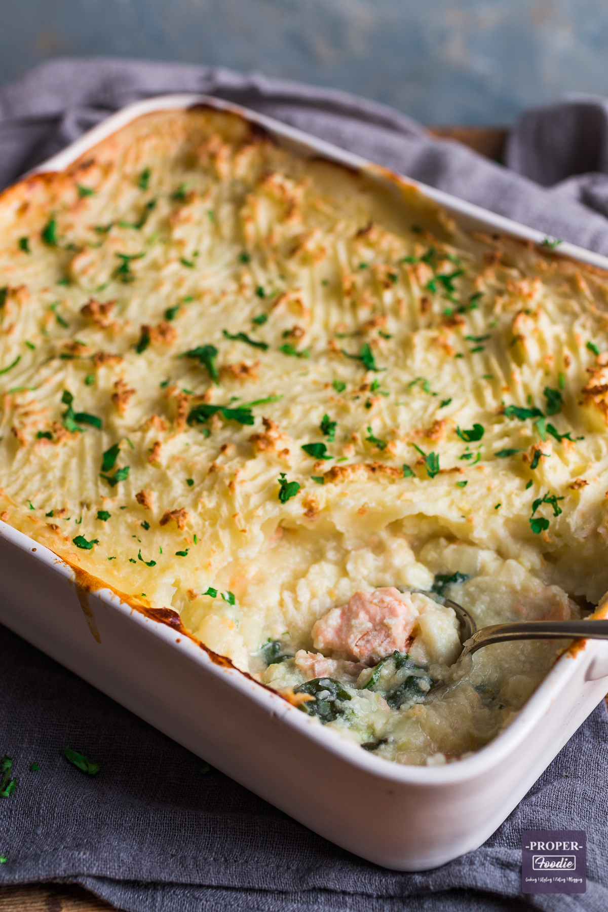 Large shallow casserole dish containing mash topped classic fish pie, baked until crisp and golden brown.