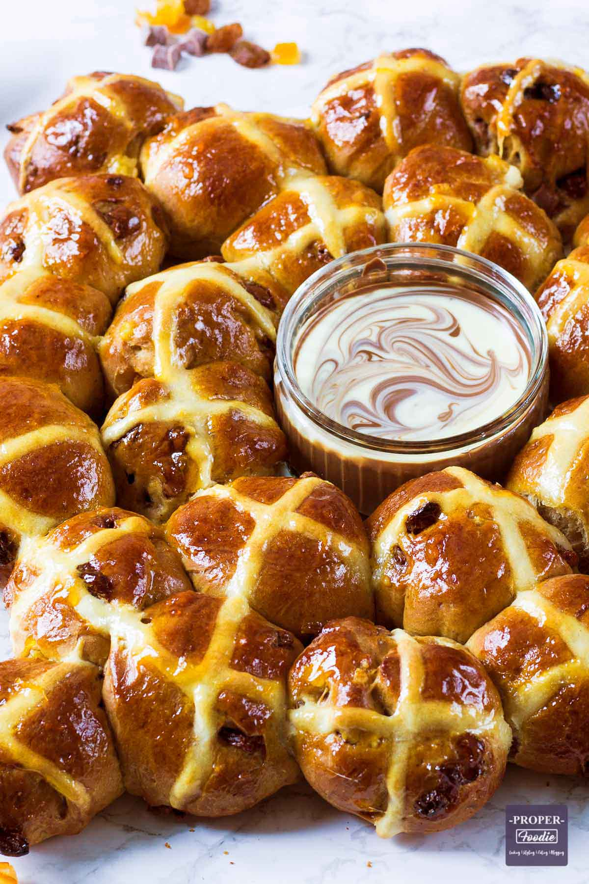 mini hot cross buns bakes in a ring shape with melted chocolate dip.