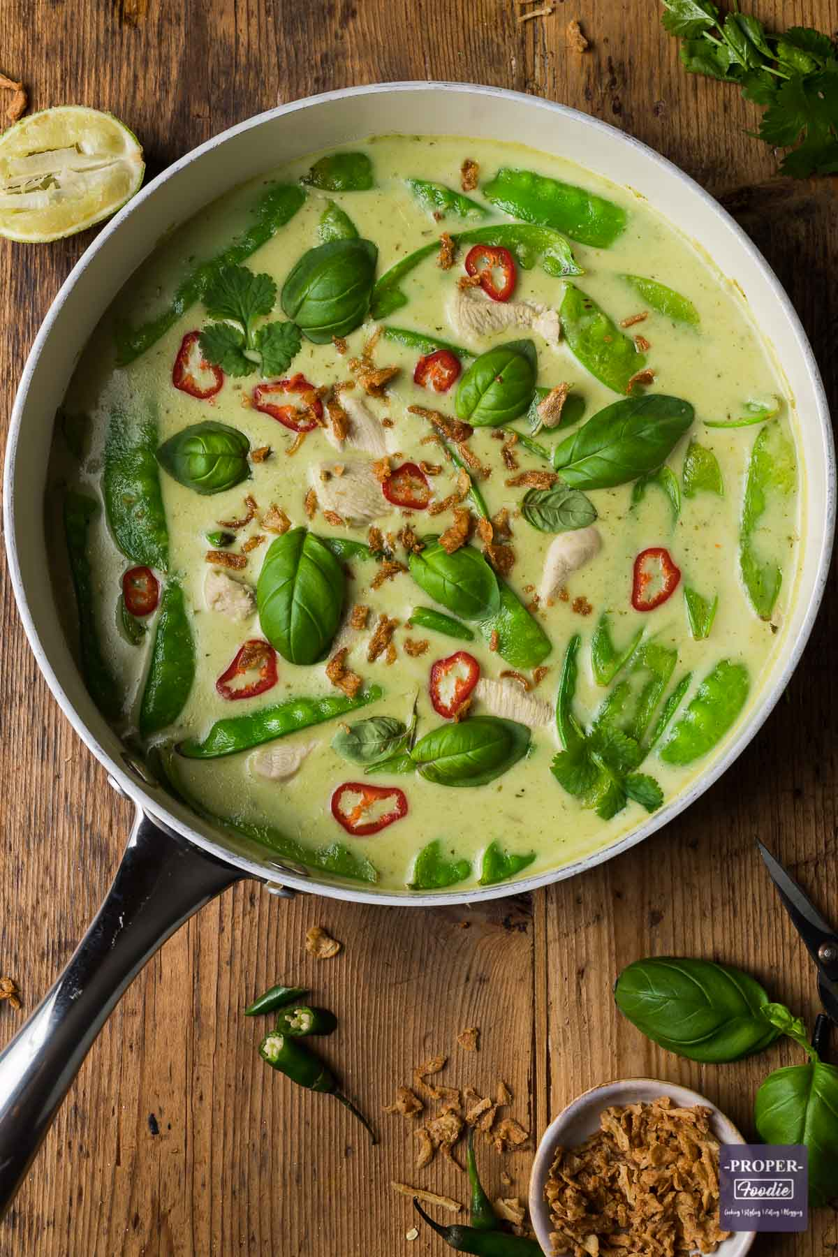 Thai green curry recipe in a large pan topped with sliced red chillies, basil leaves, coriander leaves and crispy onions