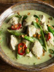 A bowl of Thai green chicken curry with mangetout, green coconut sauce and topped with sliced green chillies and crispy onions.