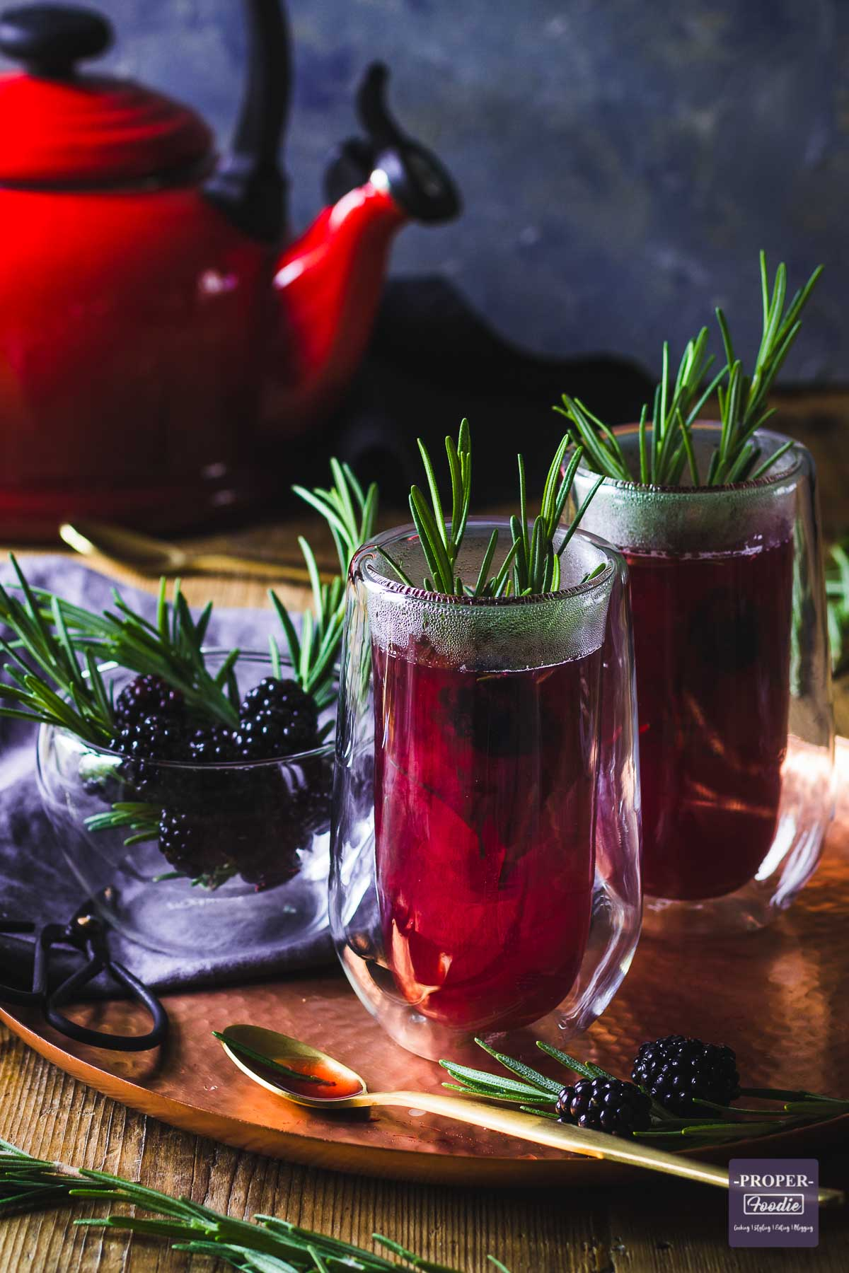 Two double wall tall glass filled with purple berry hot toddy and decorated with sprigs of rosemary.