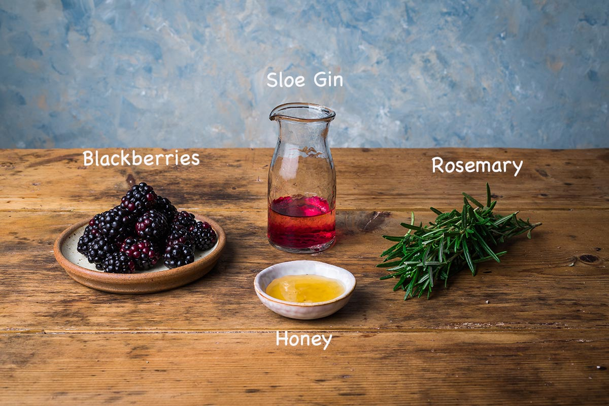 A display of the ingredients needed to make the sloe gin hot toddy recipe with text overlay stating each ingredients