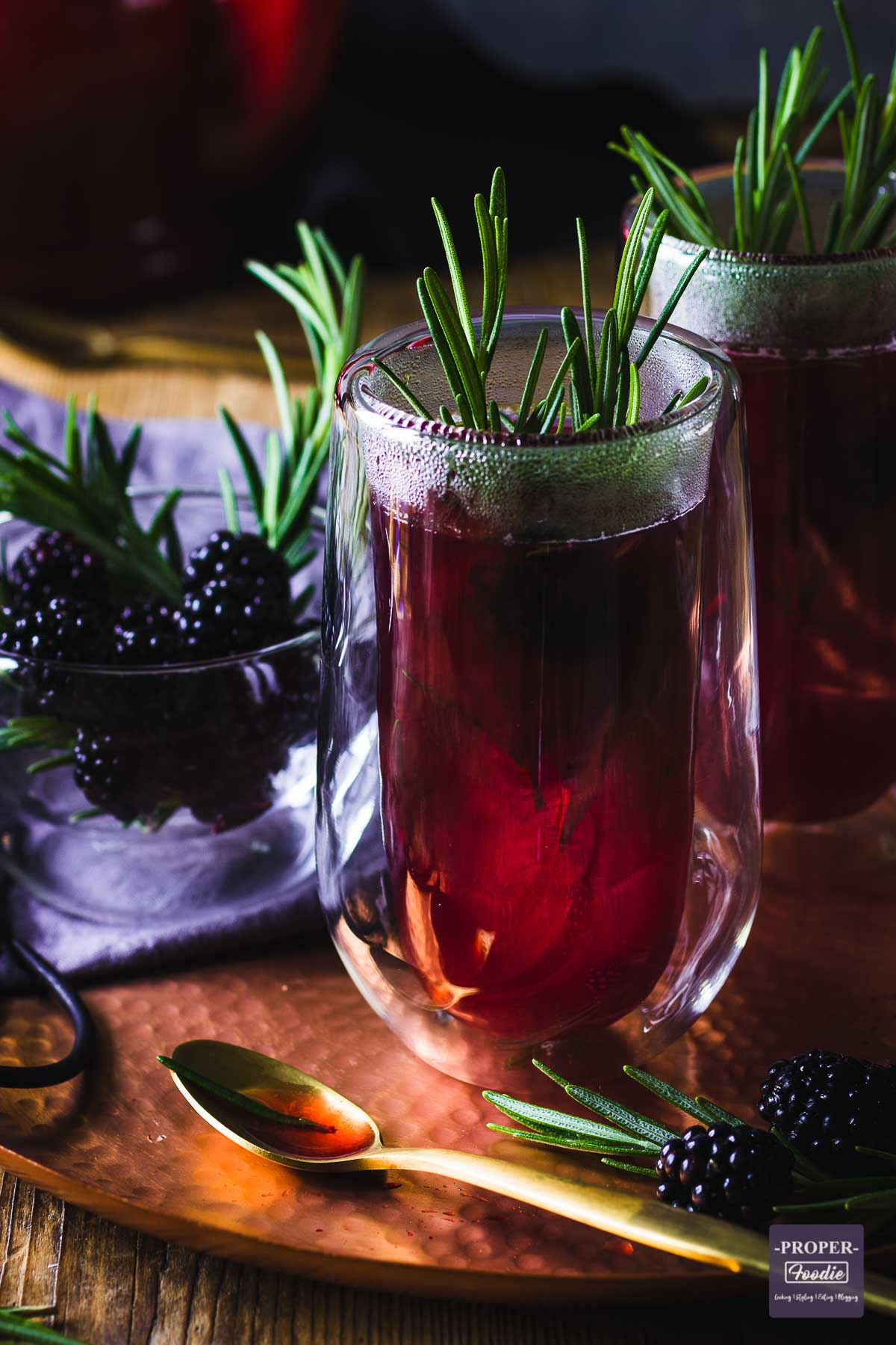 a purple and steaming, double walled glass of sloe gin hot toddy decorated with a sprig of rosemary and a second glass in the background.