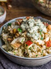 Quinoa and roasted cauliflower salad with lemon & herb dressing, served in a small bowl sat on a blue napkin.