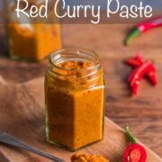 A small jar filled with homemade Thai red curry paste with a spoonful of paste in the foreground and a chopped up red chilli at the side.