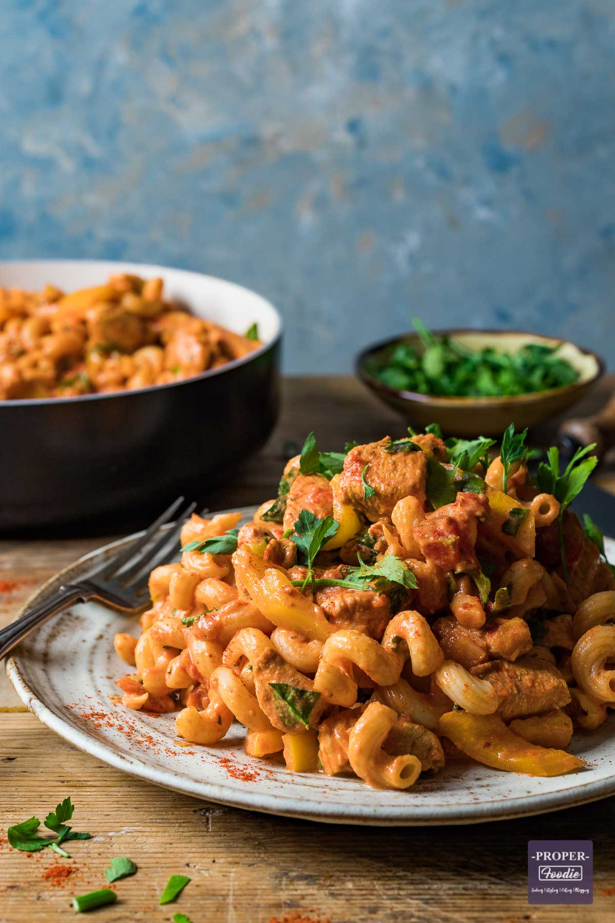 Creamy cajun chicken pasta recipe served on a plate with a pan of extra pasta in the background.