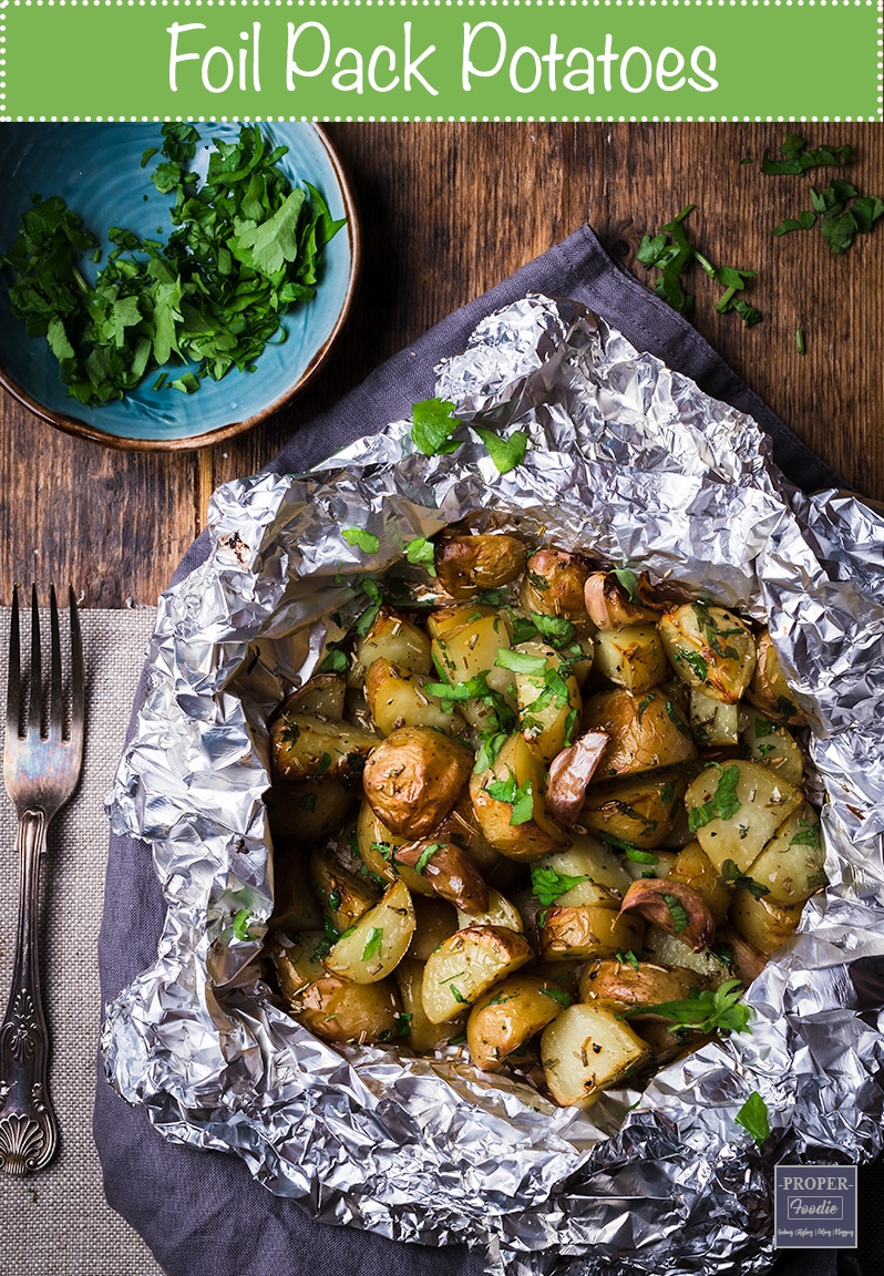 foil pack potatoes baked in the oven with garlic cloves and served with butter and parsley