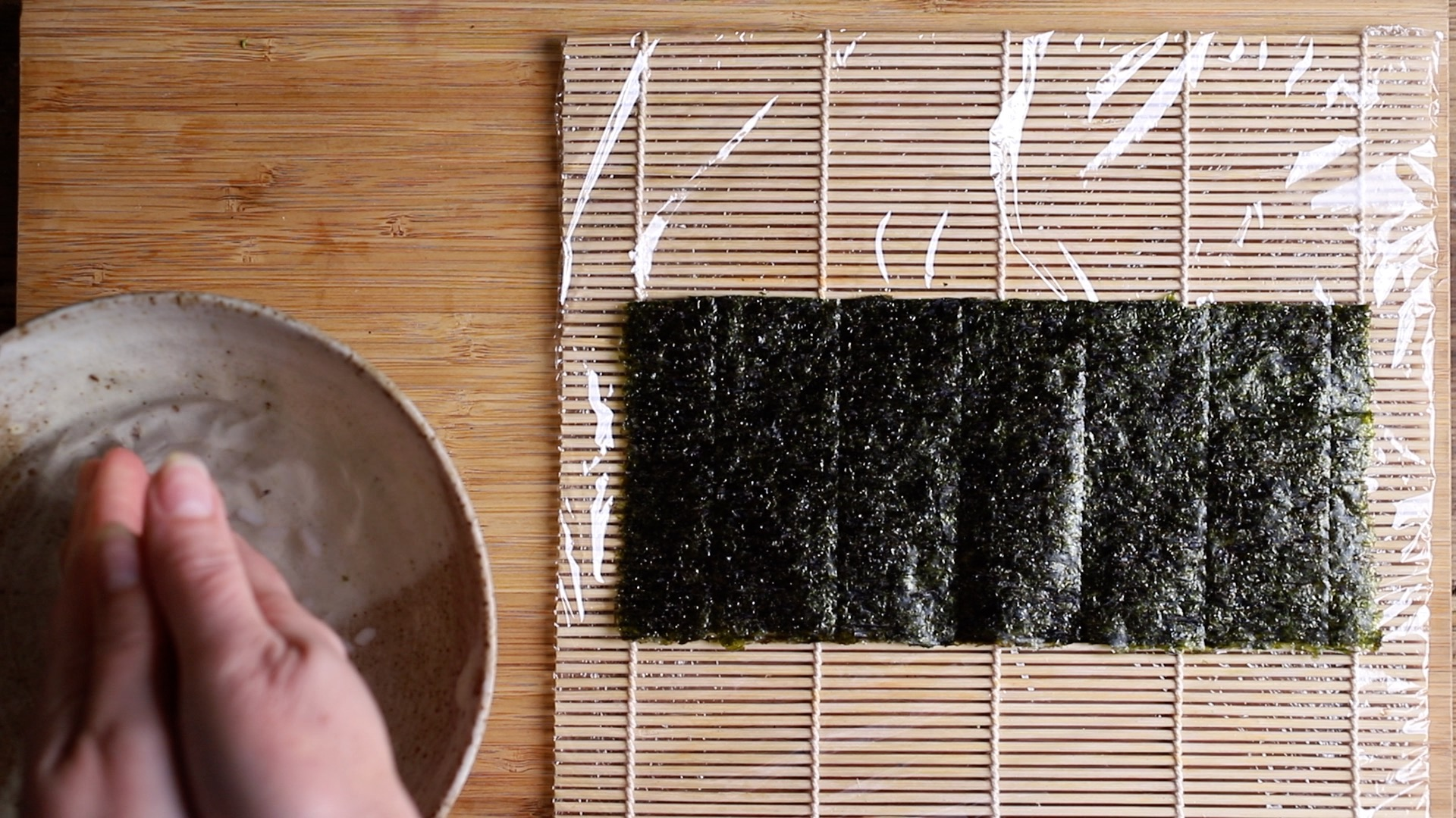 seaweed sheet in centre of bamboo mat