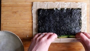 use bamboo mat to start rolling and tightening the sushi roll