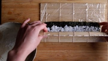 use the bamboo mat to start rolling and folding your maki sushi