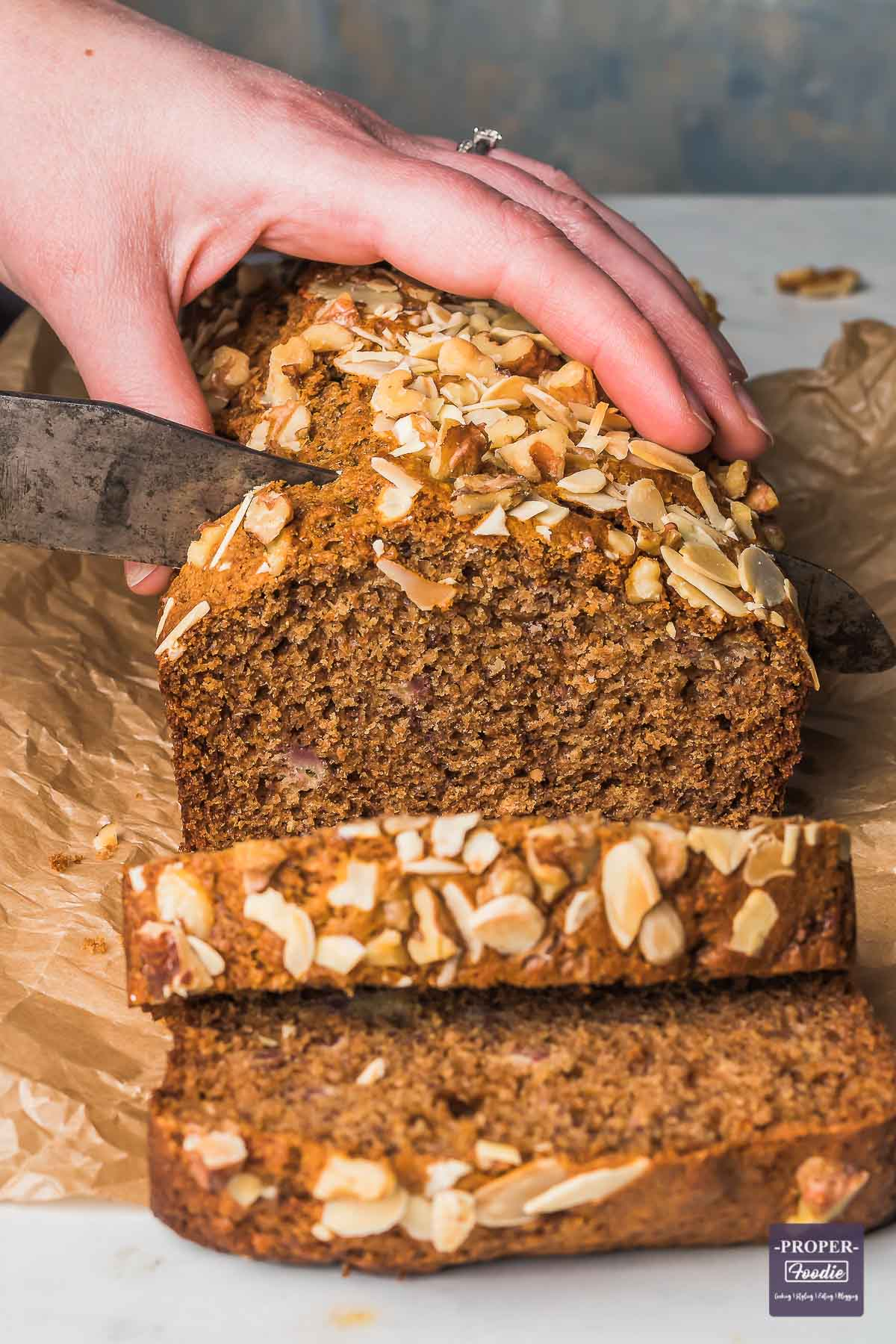 Loaf of healthy banana bread being sliced in to.