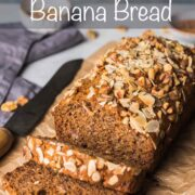 Banana bread loaf on brown crumpled paper with 2 pieces sliced and falling down from the front of the loaf.