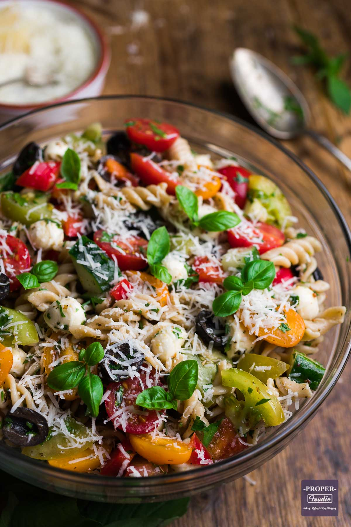 Large bowl filled with Italian Pasta Salad with a serving spoon and small bowl of grated pecorino cheese in the background.