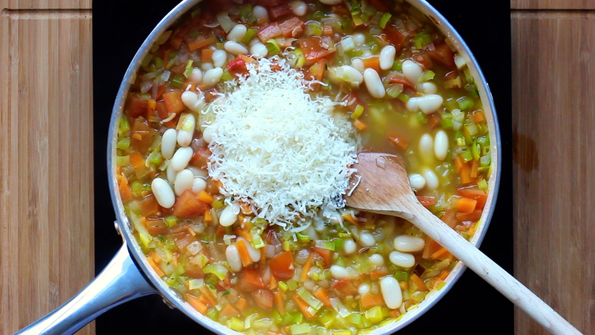 adding cannellini beans and parmesan to the soup
