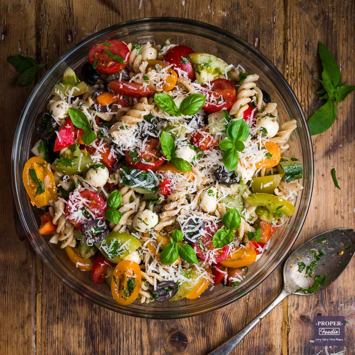 Large bowl filled with cooked fusilli pasta, colourful tomatoes, cucumber, mozzarella pearls and topped with basil leaves and grated pecorino.