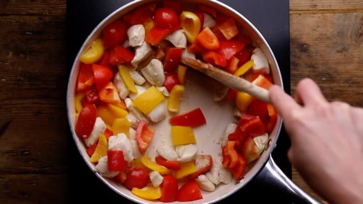 tomatoes and red and yellow peppers added to the chicken