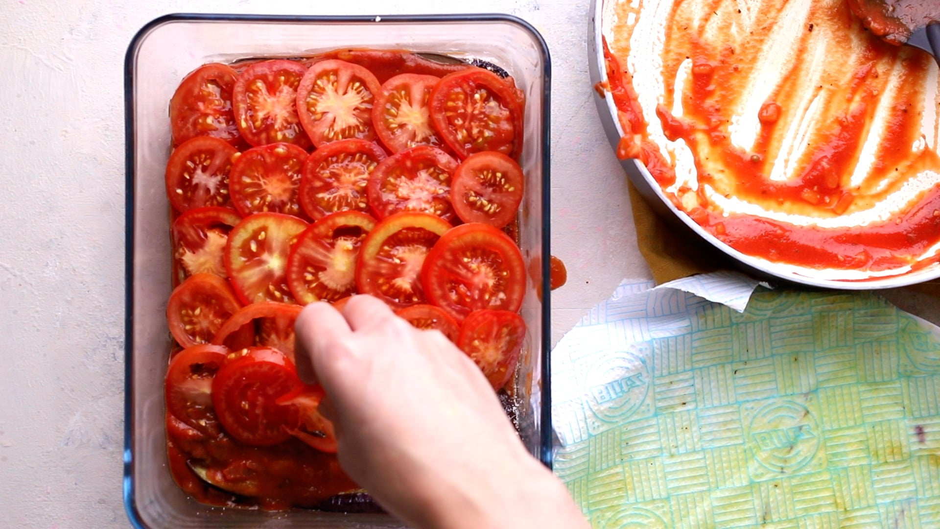 adding a final layer of sliced tomatoes