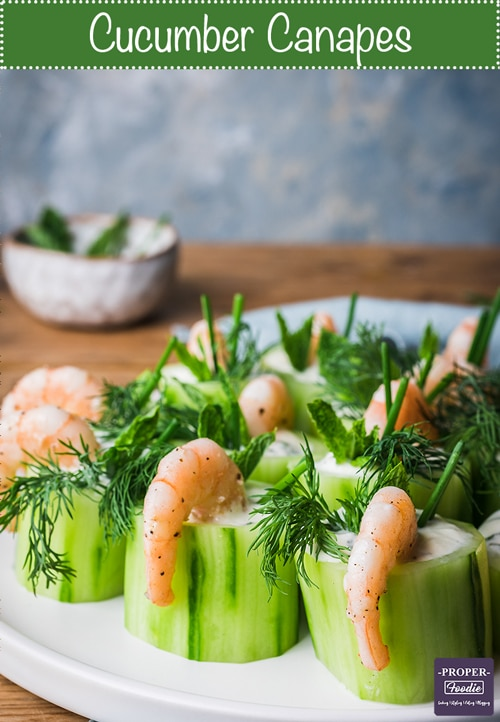 Create a classic easy finger food by making these cucumber canapes with prawns! these fancy appetisers are easy to prepare with a refreshing tzatziki filling, flavourful prawns and vibrant herb topping. Serve these for a party and your guests will be asking you for the recipe.