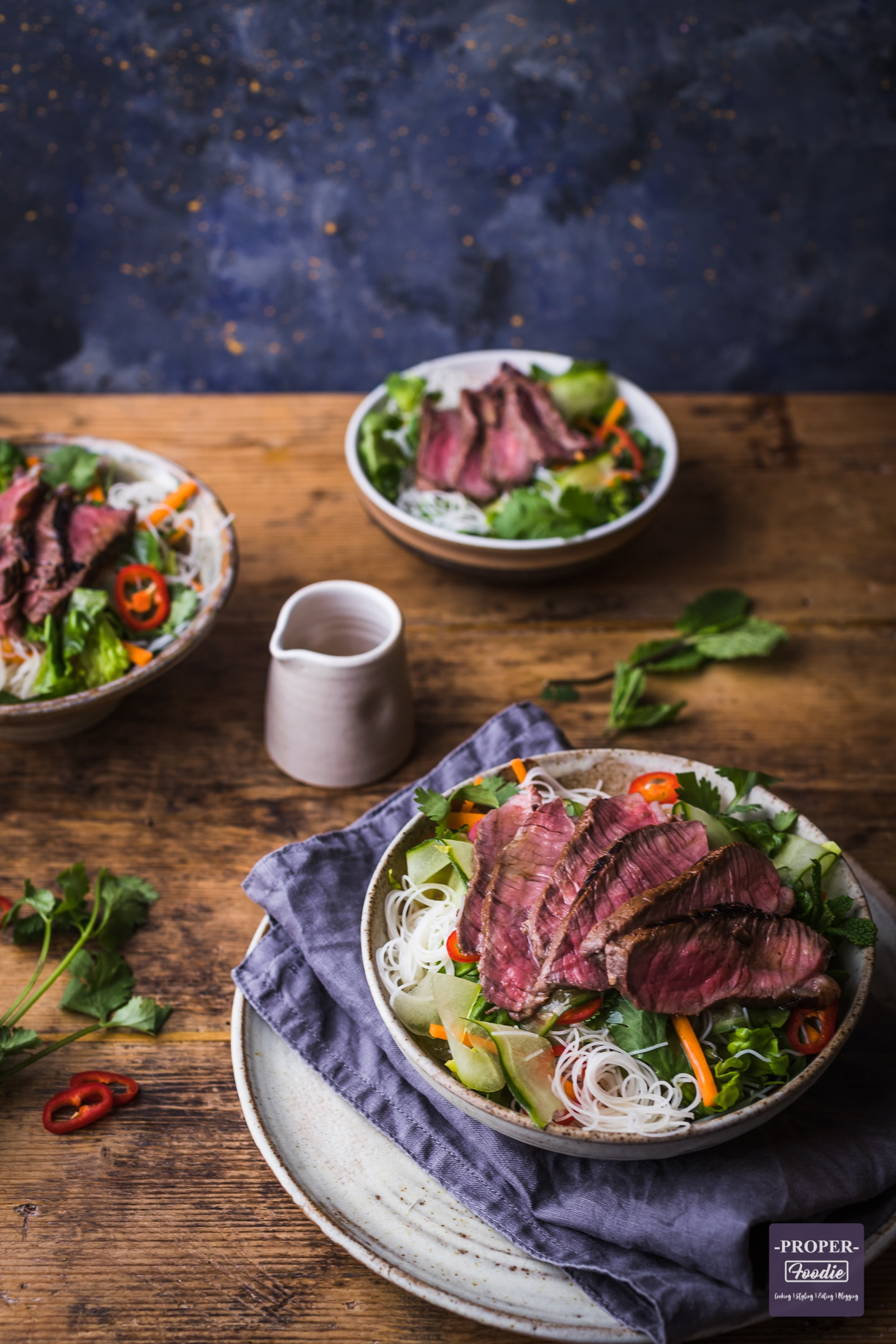 Beef noodle salad served up in 3 bowls with a small jug of salad dressing in the centre