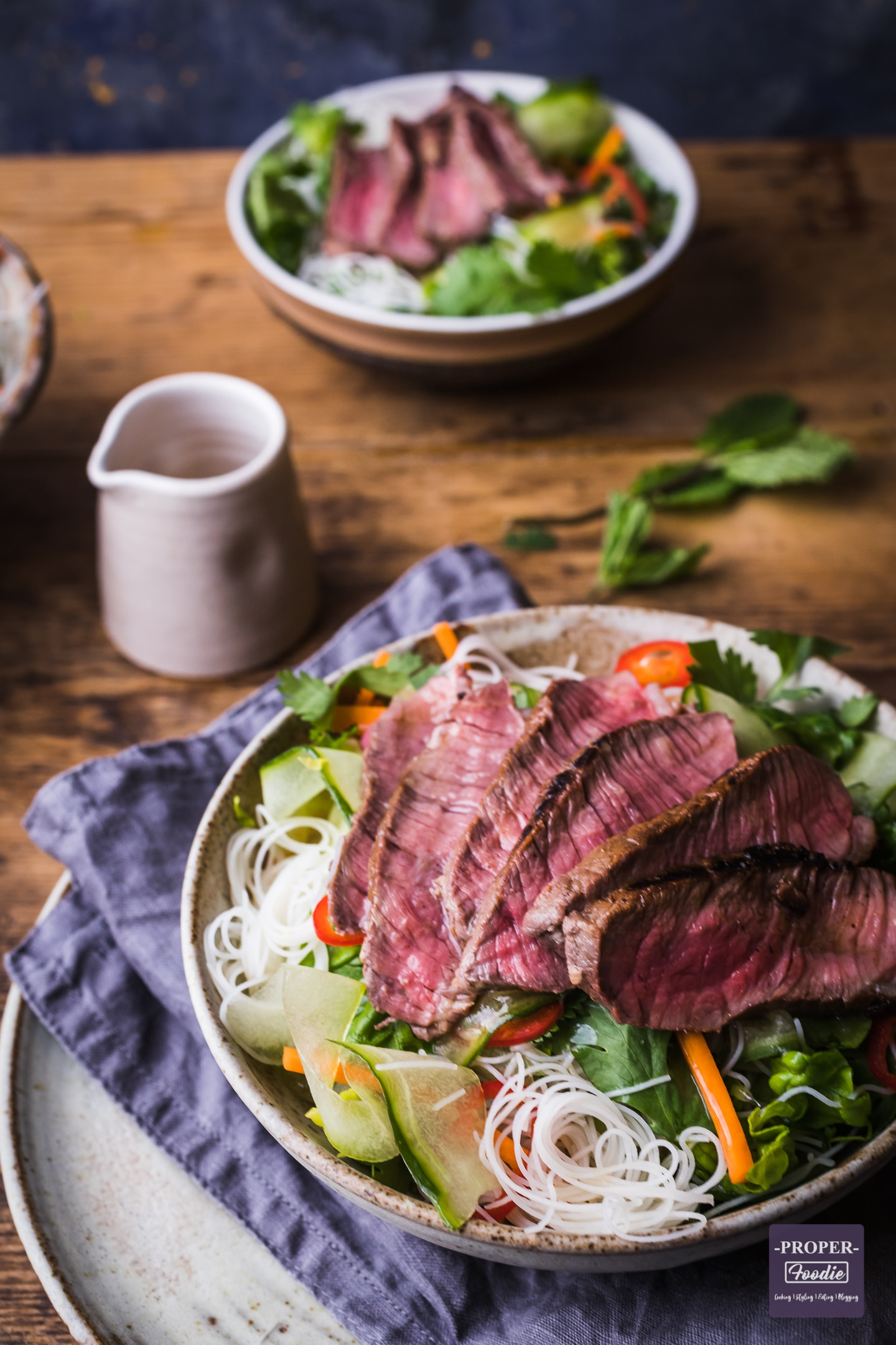 Slices of rare steak over rice noodles and salad in a bowl