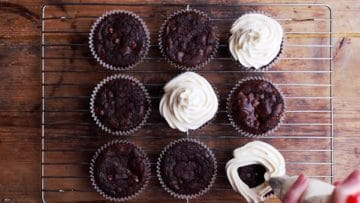 piping mascarpone cream onto chocolate muffins