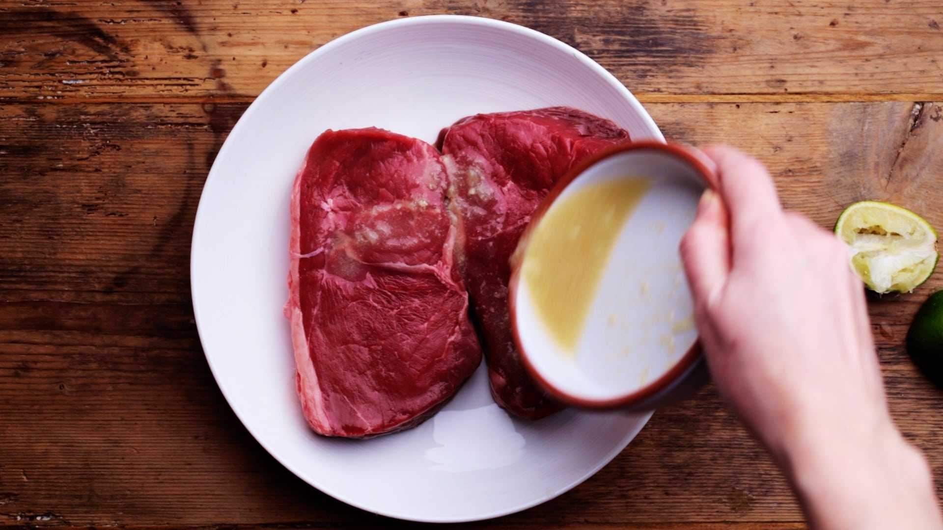pouring lime marinade over steaks