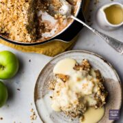 A portion of apply crumble on a small plate with custard drizzled over and the rest of the crumble in a larger dish with a spoon.