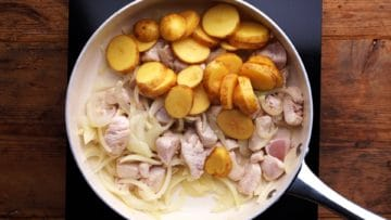 Sliced potatoes added to fried chicken and onions