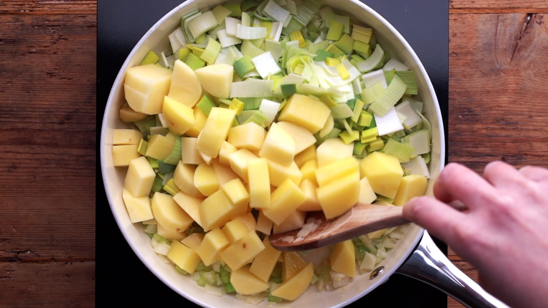 chopped leeks and cubed potatoes added to pan