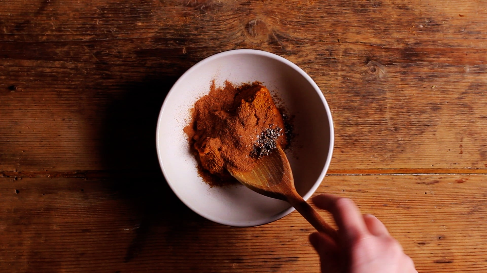 adding spices to a bowl