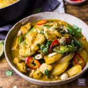 A bowl of massaman curry with sliced new potatoes and chunks of chicken.