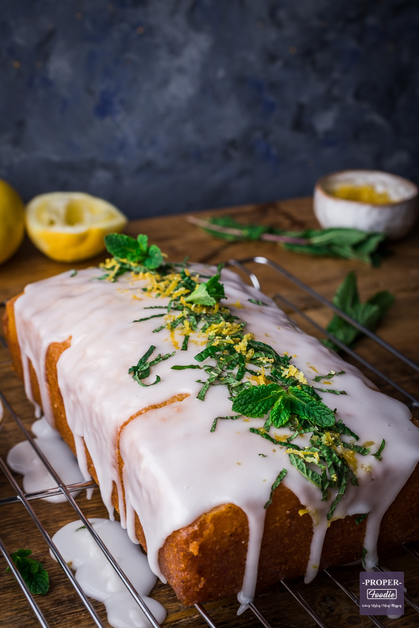 Lemon drizzle cake with lemon icing and topped with lemon zest and mint