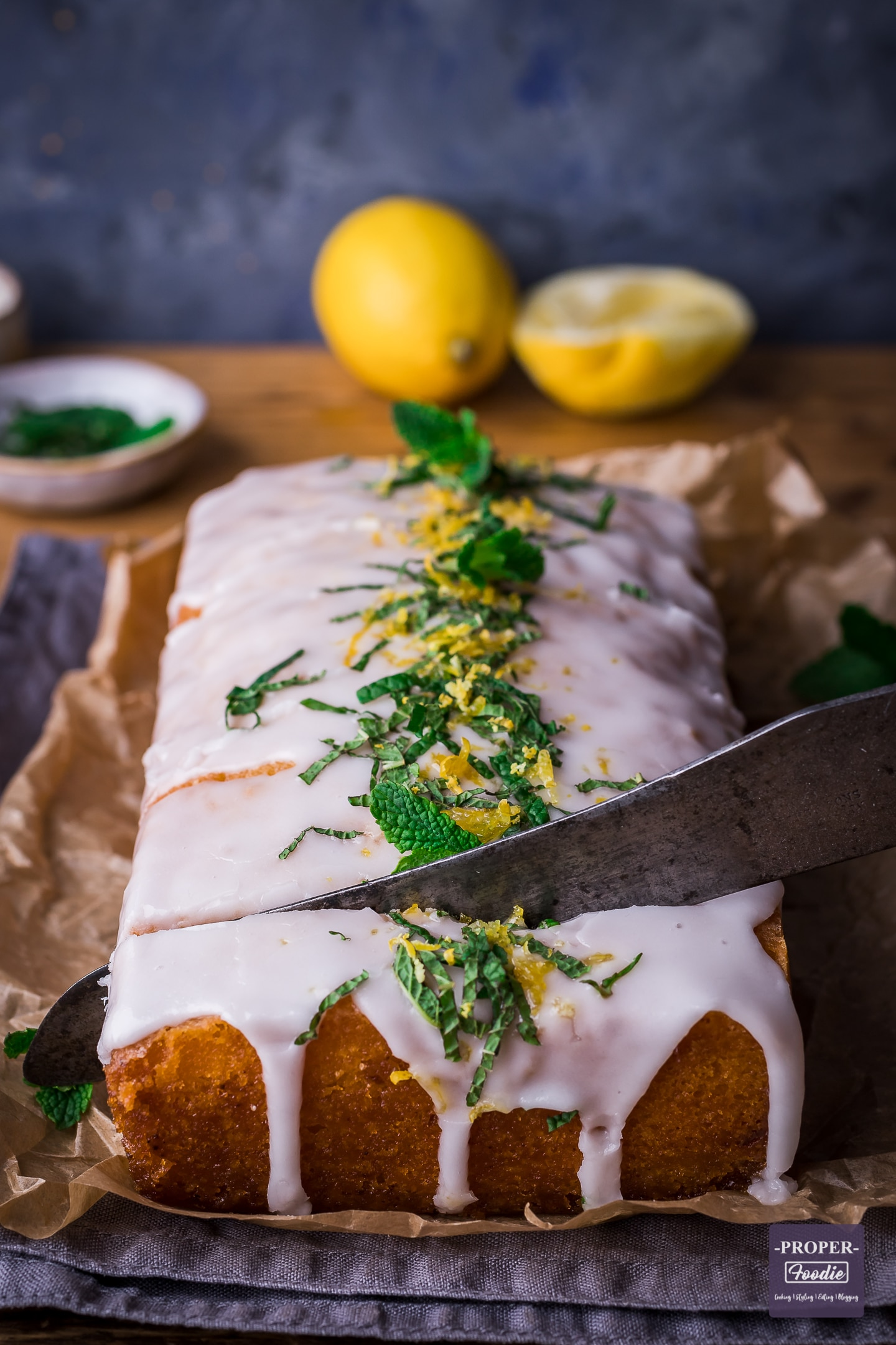Lemon drizzle cake with lemon icing being sliced into with a knife