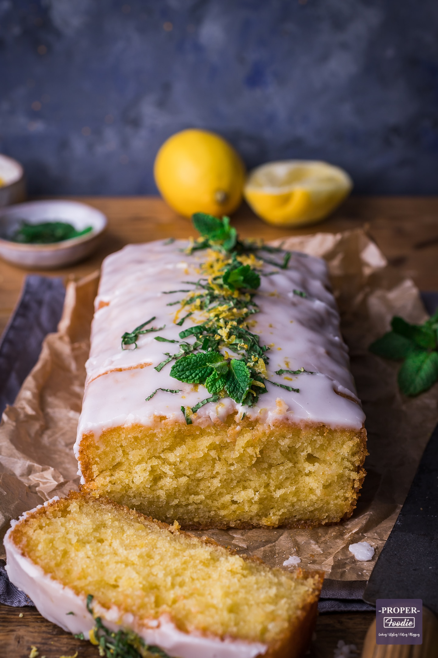 lemon drizzle cake with one piece sliced off at the front and lemons and fresh mint in the background