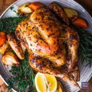 whole chicken roasted and presented on a large plate with cooked carrots and onions and fresh herbs.