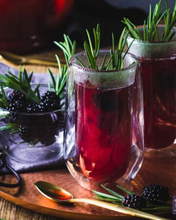 purple and steaming sloe gin hot toddy served in 2 double wall glasses, with sprigs of rosemary and on a bronze tray.